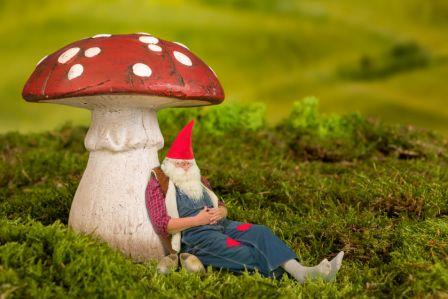 36930457 - sleepy garden gnome lying under a fairy tale toadstool